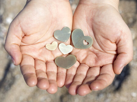 Two hands are holding five small beautiful bright heart shapes.