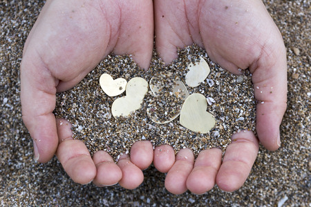 shallow: Two hands are holding five small beautiful bright heart shapes and sand.