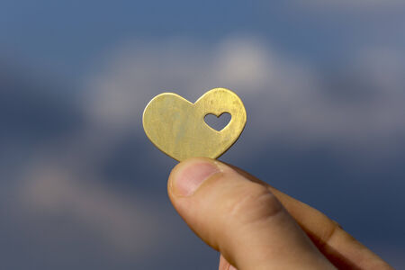 A hand is holding a beatiful bright heart shape with a small heart in it, on the backdrop of a blue sky with clouds. Stok Fotoğraf