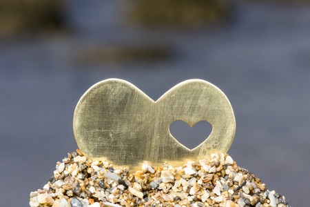 A bright beautiful metal heart is placed on top of a small sand hill. In the background is a rocky beach and waves.
