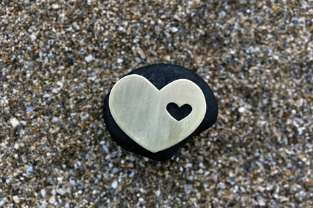 shallow: A small bright metallic heart shape is placed on a black stone on dark sand background.