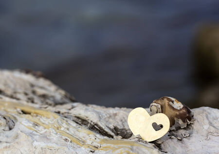 A bright beautiful metal heart is placed on top of a rock. In the background is a rocky beach and waves.
