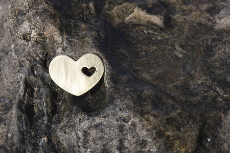 A bright beautiful metal heart is placed on a dark wet rock on a beach.
