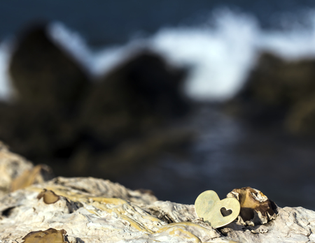A bright beautiful metal heart is placed on top of a rock. In the background is a rocky beach and a breaking wave. Stok Fotoğraf