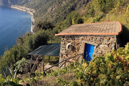 A small stone house with a blue door is located high above the sea. photo