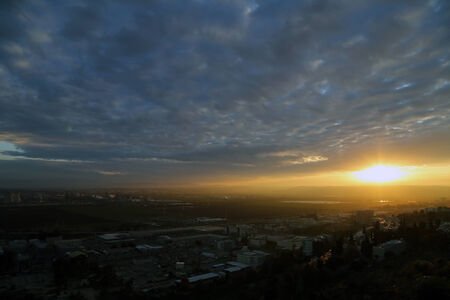 alpine zone: The Sun is rising over fields and a city. The sky is cloudy and dramatic.