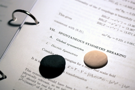 white pebble: A black pebble and a white pebble are photographed on the background ofa science essay discussing symmetry breaking. Stock Photo