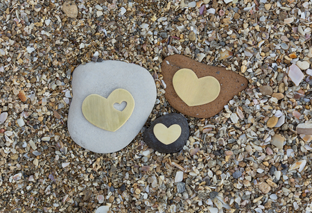Three bright beautiful metal hearts are placed on three different rocks on sandy background.