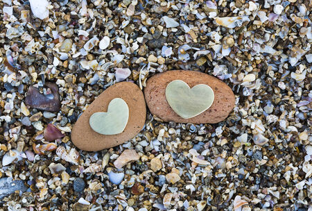 Two bright beautiful metal hearts are placed on two red rocks on sandy background.