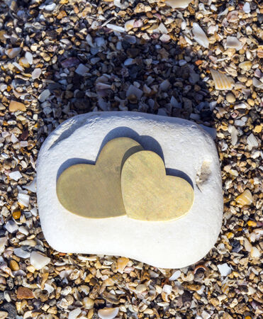 portrait orientation: Two bright beautiful metal hearts are placed on a bright rock on sandy background. Portrait orientation.