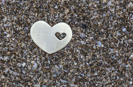 A small bright metallic heart shape is placed on dark sand background. Stok Fotoğraf