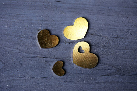 spread around: Four bright metal hearts on a wooden table. Metal dust is spread around the hearts. Stock Photo