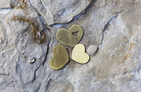 Three bright beautiful metal hearts are placed on a rock with natural salt on a beach.