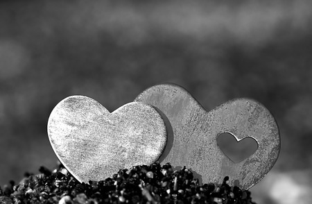 Two bright beautiful metal hearts are placed on top of a small sand hill. The background is diffuse beach and waves.