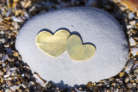 Two bright beautiful metal hearts are placed on a bright rock on sandy background.