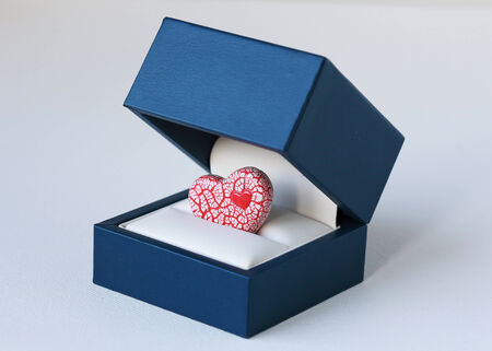 jewelry box: An image of a bright red and white ceramic heart inside a blue jewelry box, symbolizing a romantic proposal