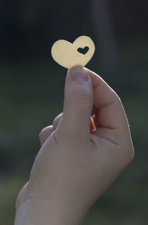 A hand is holding a metal heart shape with a small heart cut inside it. The sun creates a lens flare. Stock fotó