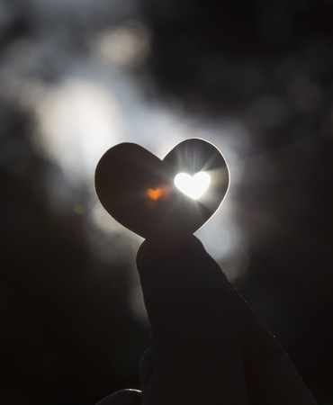 A hand holds a heart shape with a small heart shape inside it against the sun. A small heart ghost image appears.