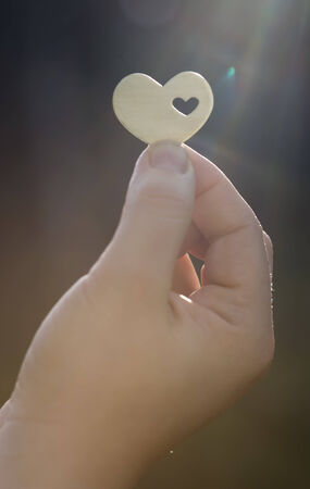 A hand is holding a metal heart shape with a small heart cut inside it. The sun creates a lens flare. photo