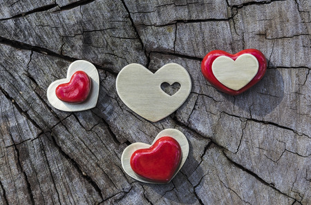 speckle: Red ceramic and metal hearts are placed on flat wood. Stock Photo