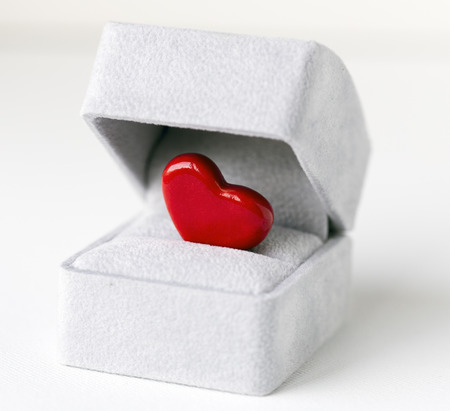 jewelry box: An image of a bright red ceramic heart inside a grey jewelry box, symbolizing a romantic proposal