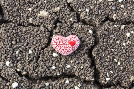 A red ceramic speckled heart with a small heart inside it is placed on dry soil.