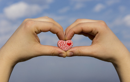 Two female hands are holding a bright red speckled ceramic heart against the blue sky with clouds. photo