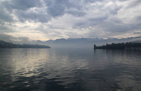 Lucern Lake (Switzerland) in mist on the backdrop of mountains and clouds. photo