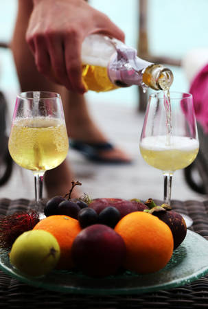 A man's hand pours champagne into two glasses. A plate of exotic fruits is in the front. Standard-Bild