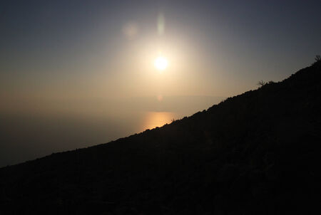 sillouette: The sun rises over the Dead Sea. A black mountain sillouette is in the front.
