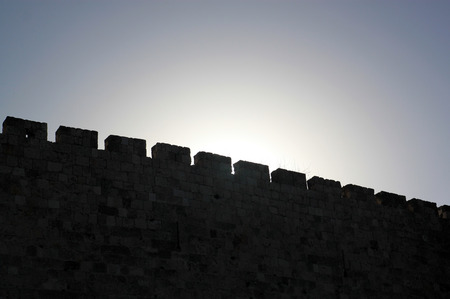 Ancient wall is lit by the Sun, forming a dark silhouette.