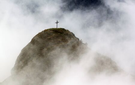 engulfed: A single cross stands on a moutnain engulfed in white clouds.