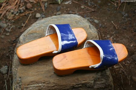 ryokan: Traditional Japanese Zen Wooden Shoes on a Rock in a Garden. Stock Photo