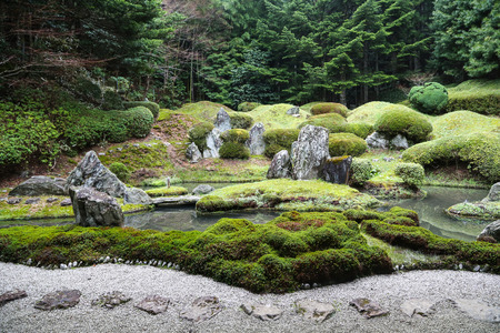 Vreedzame Japanse Zen-tuin met vijver, rotsen, grind en Moss