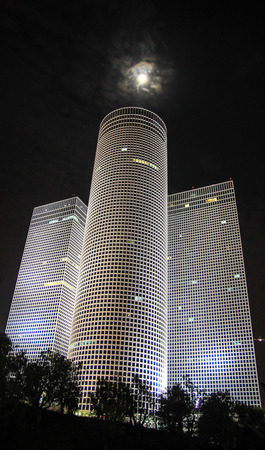 Azrieli Towers in Tel Aviv at night with moon