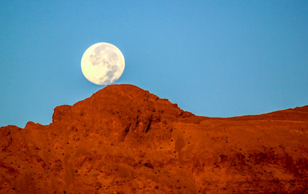 Moon rises above a hill in the desert.