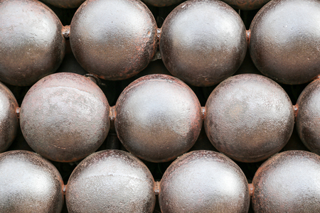 artillery shell: Cannon Balls arranged in a pile background.