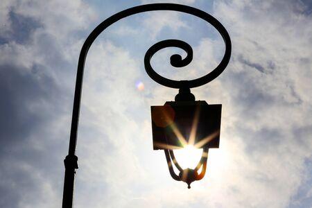 Antique lamp post with Sun shining through the lantern.