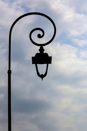 Antique lamp post with clouds background.