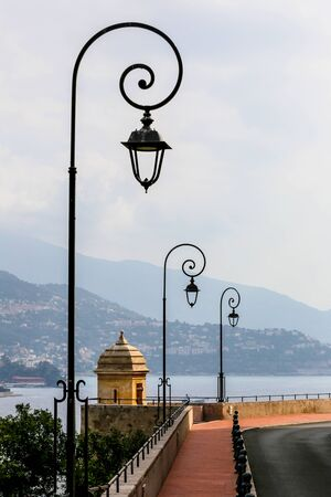 Antique lamp posts along a street with sea view in Monaco Stock Photo