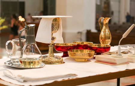 Gold chalices and bowl in a church at mass.
