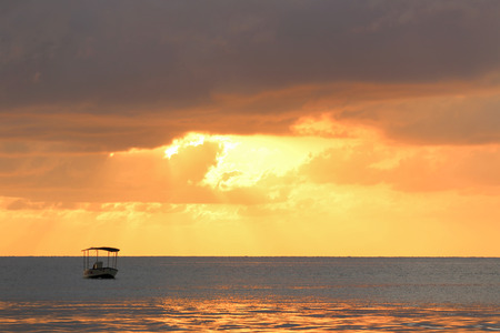 Ocean sunset with clouds in gold colors  with boat silhouette.
