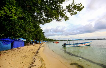 Shoreline in Jamaica with boat and closed merchant booths. Reklamní fotografie