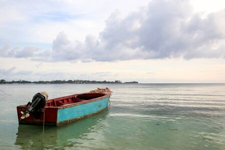 Boat close to the shore with clouds and clear calm water. Stock Photo