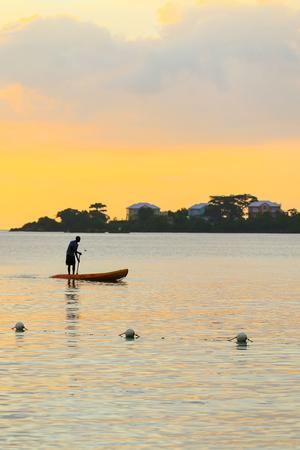 Silhouet van de mens roeien standng op een boot bij zonsondergang tijd. Stockfoto
