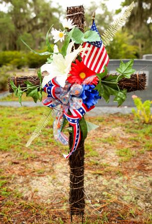 Confederate ribbon on a wooden cross with flowers at a cemetary.