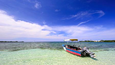 Boat in an ocean close to the beach. Reklamní fotografie