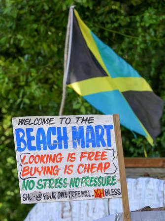 Jamaican flag at a beach market with sign.
