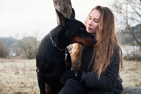 portrait of beautiful young woman with her doberman dog. Warm natural color.