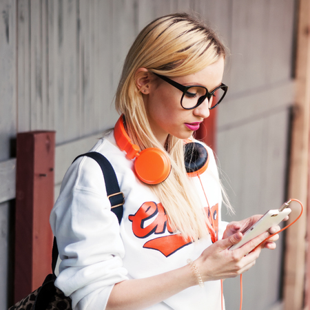 Girl with orange headphones looking for awesome track in her phone. Street shoot, music energy, lifestyle, european or american style, clear sound, sunshine, outdoors